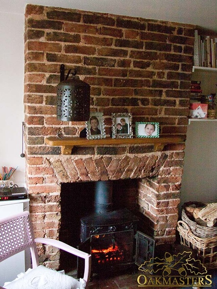 A small brick fireplace with an oak mantle shelf and corbels