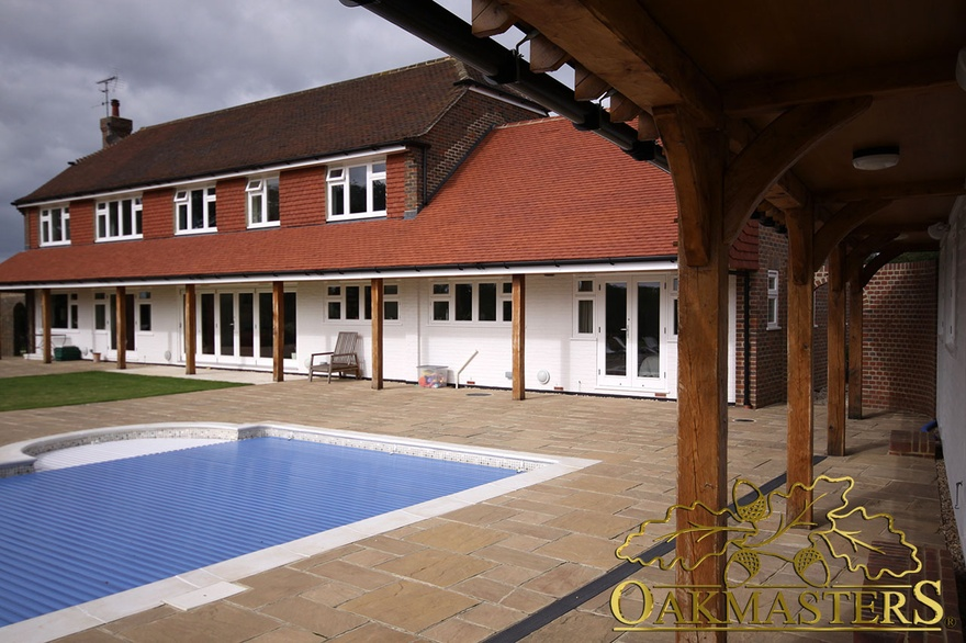 Country house extension with oak columns supporting roof extension