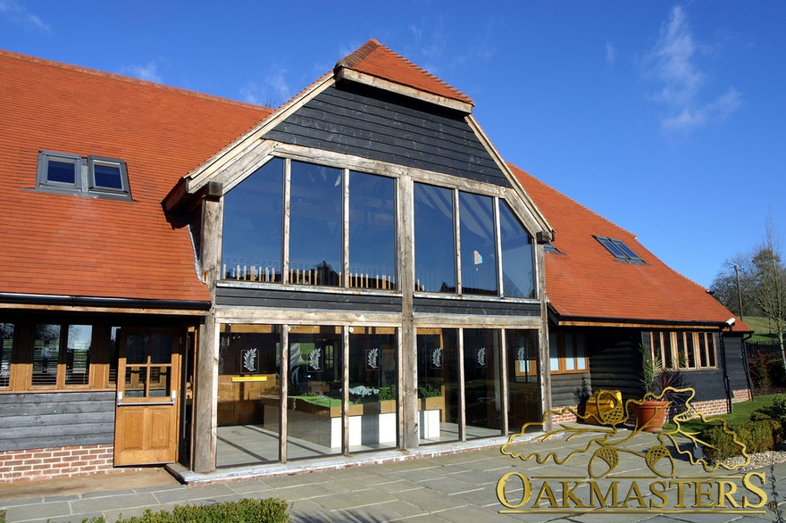 Double height oakframed glazing under timber clad hip roof