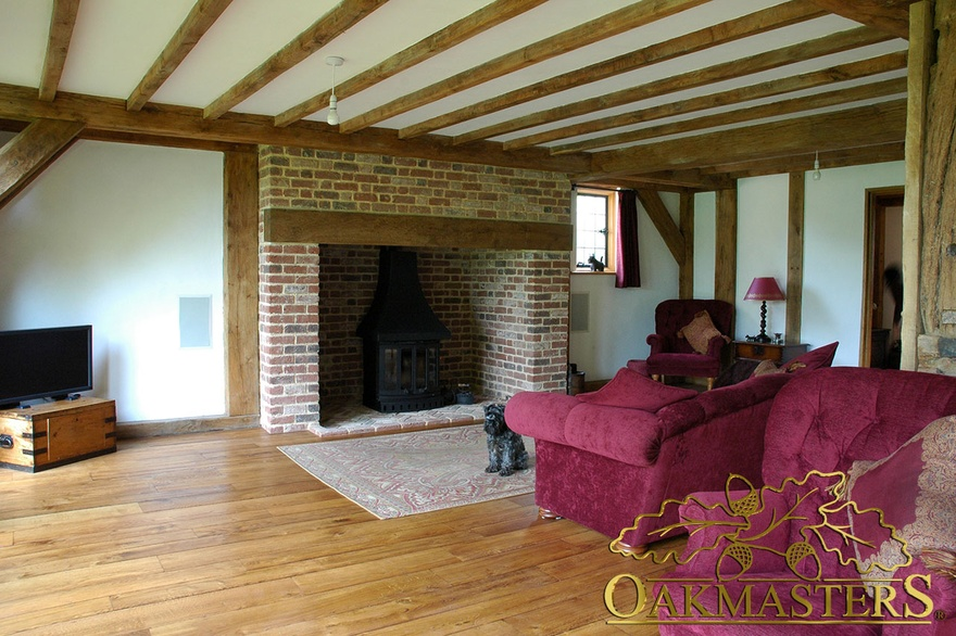 Oak ceiling beams and mantle above large brick fireplace in glazed sitting-room extension