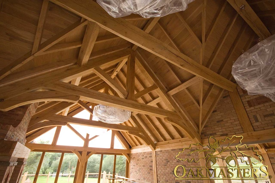 Extensive exposed oak ceiling with raised tie trusses and glazed gable end in country house