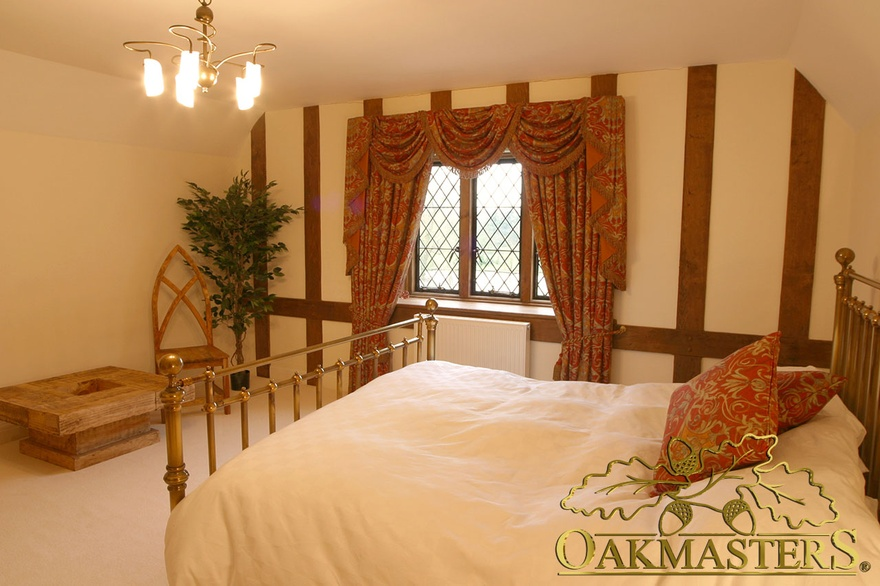 Oak cladding creates a feature wall in this bedroom