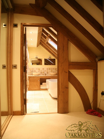 Queen post truss forms part of the doorway into this loft bathroom