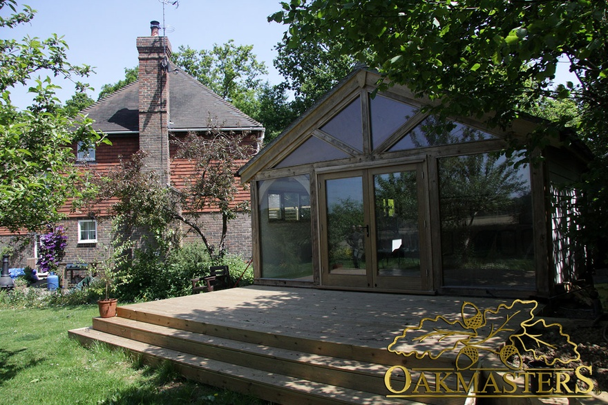 Glazed gable and full height windows lead to wooden patio on garden room and garage complex