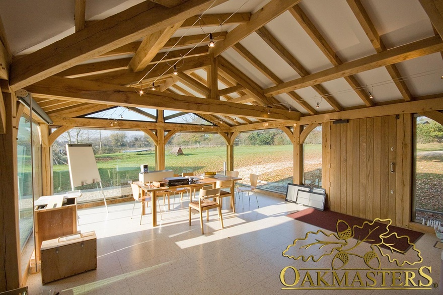 Interior of garden room office with exposed oak vaulted ceilings and full height glazed windows to maximise light and views