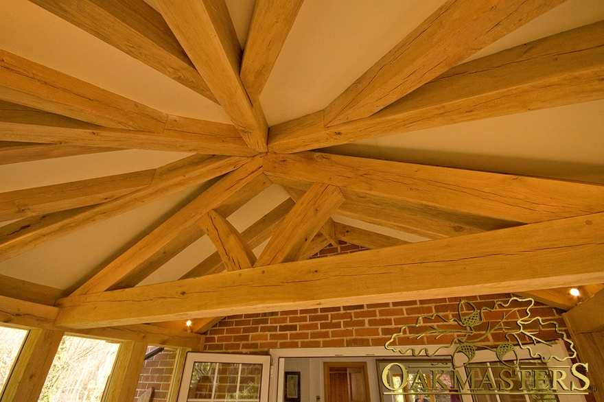 Detail of handcrafted oak beams rafters and truss in hexagonal garden room