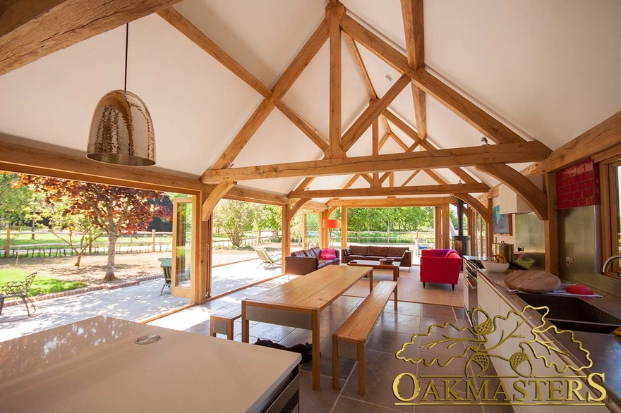Modern kitchen with oak frame exposed truss open ceiling and oak frame glazing