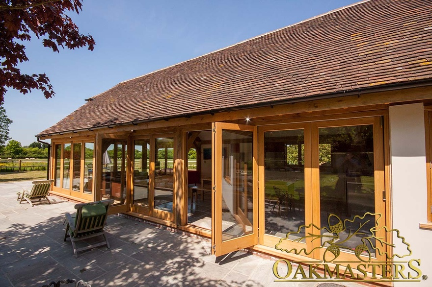 Exterior of modern garden room kitchen with open glazed bi-fold patio doors