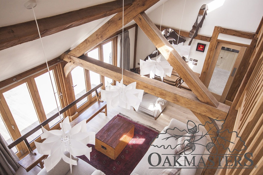 View down from the landing into the lounge area through a large oak king post truss