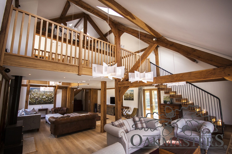 Living room in its full glory with oak posts, vaulted ceiling, gallery landing and a glazed oak truss in the background