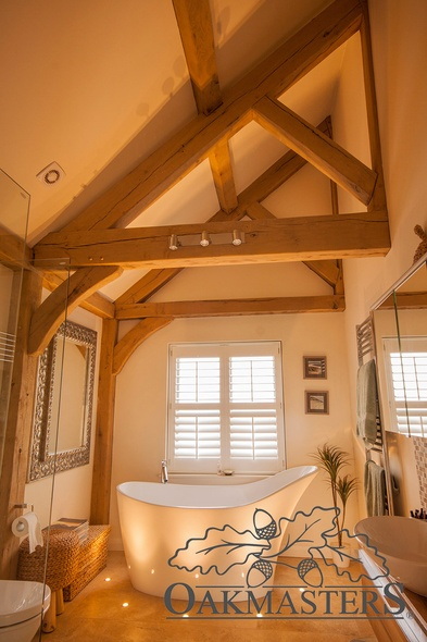 Upstairs in the oak extension, the en-suite bathroom features beautiful structural beams and exposed oak trusses