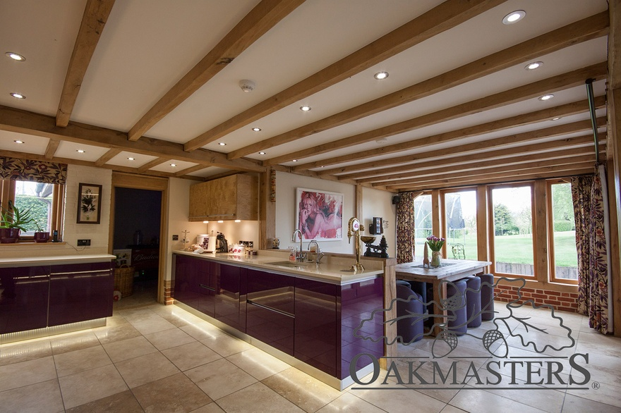The open plan kitchen diner has a large oak window flooding the dining area with natural light