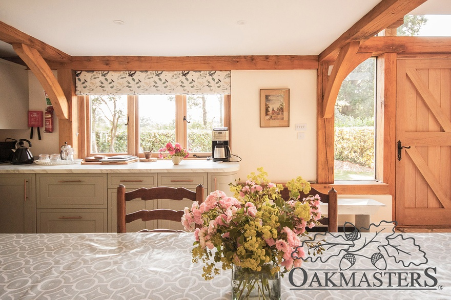 Open plan kitchen and dining area are framed with oak beams and posts.