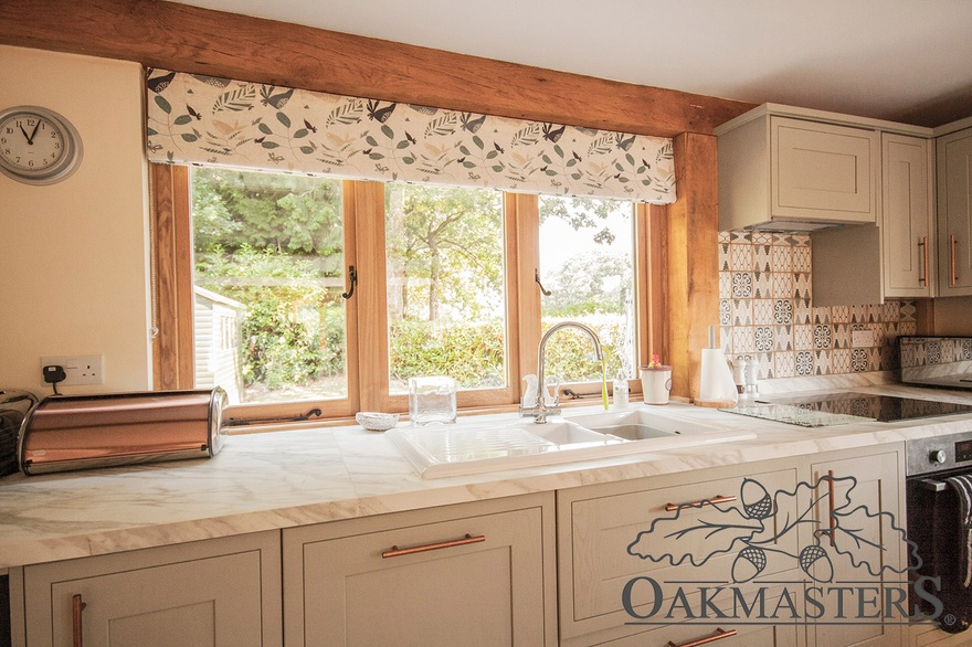 The kitchen windows are inset in the green oak structural frame.