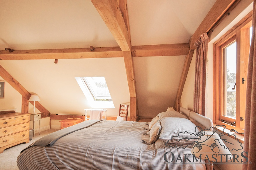 Vaulted ceiling with an oak truss create a lovely traditional feel in this bedroom.