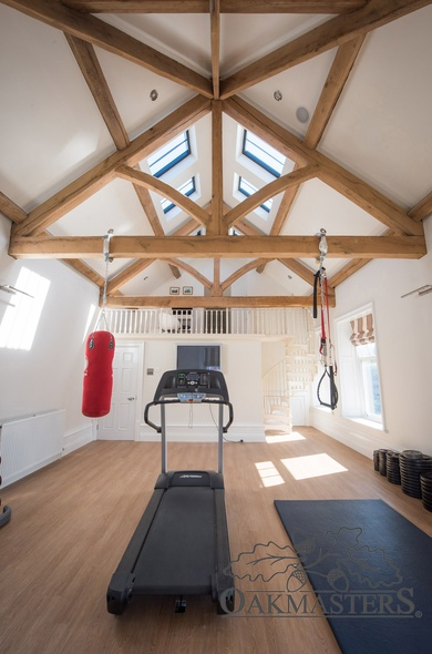 The gym room's oak ceiling allows natural light to flood in through the roof lights