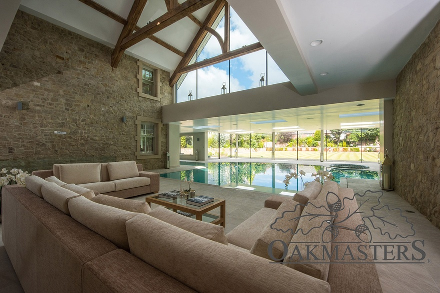 Lounging area overlooking to pool also has a view of glazed oak truss