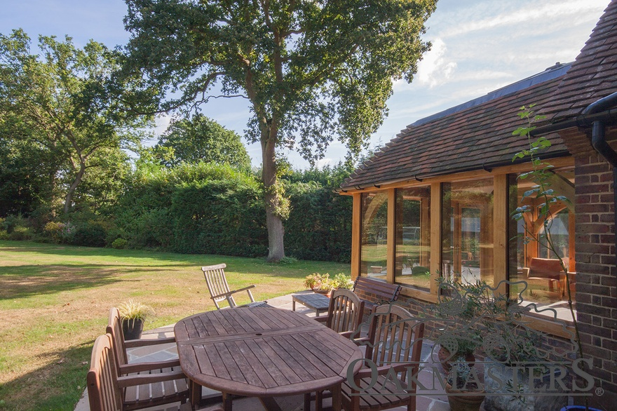The patio outside the oak framed orangery has an outdoor dining space